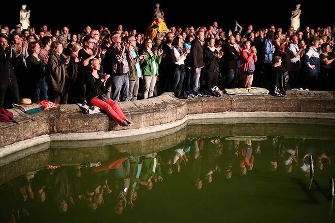 Publikum hinter einem Brunnen