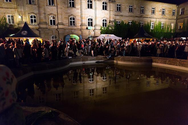 Publikum von Haindling hinter einem Brunnen
